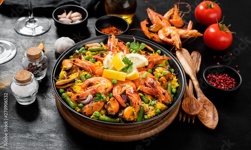 Canvastavla Traditional spanish seafood paella in the fry pan on a black wooden  table