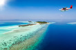 Wasserflugzeug fliegt über eine Insel auf den Malediven im Indischen Ozean mit türkisem Wasser und Korallenriff