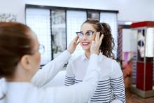 Female Optician Putting Eyeglasses On Beautiful Caucasian Smiling Brunette. Optician Shop Interior.