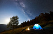 Leinwandbild Motiv Tourist camping near forest at summer night. Illuminated tent and campfire under magical night sky full of stars and Milky way. On background big tree, beautiful starry sky, mountains and full moon