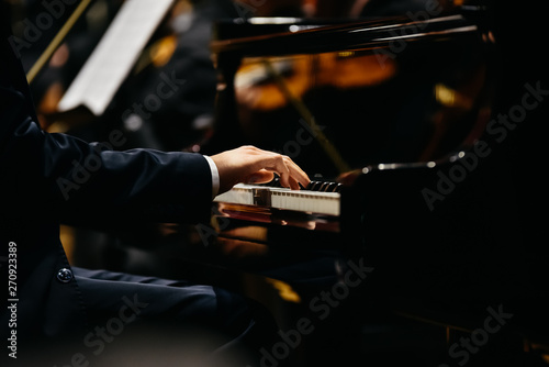 Obraz na plátně Pianist playing a piece on a grand piano at a concert, seen from the side