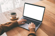 Leinwandbild Motiv Mockup image of a woman using and typing on laptop computer keyboard with blank white desktop screen with coffee cup on wooden table