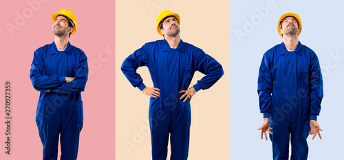 Fotografiet  Set of Young workman with helmet stand and looking up on colorful background