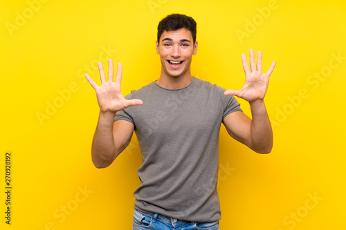 Photo  Handsome man over isolated yellow wall counting ten with fingers