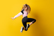 canvas print picture - Urban Ballerina dancing over isolated yellow background and jumping