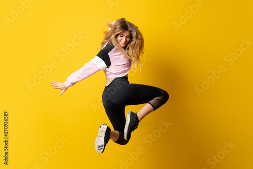 Deurstickers Dance School Urban Ballerina dancing over isolated yellow background and jumping