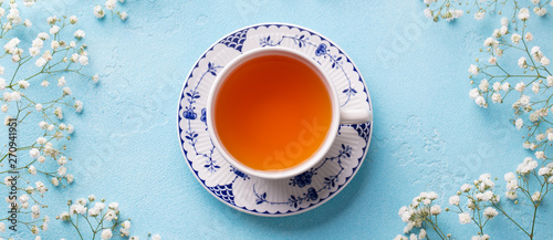 Carta da parati Cup of tea with fresh flowers on blue background