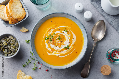Fotografie, Tablou  Pumpkin and carrot soup with cream on grey stone background