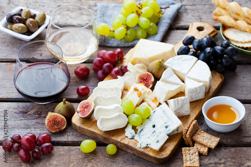 Cheese and fruits assortment on cutting board with red, white wine on wooden background Canvas Print
