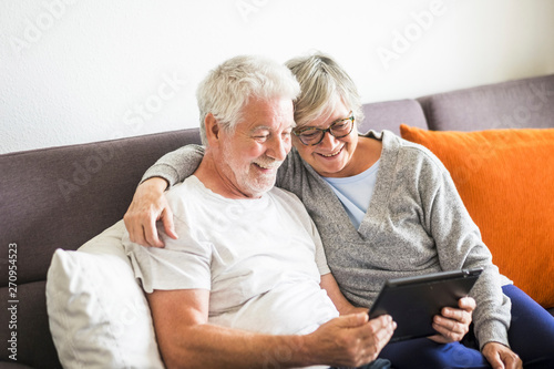 Fotografie, Obraz  couple of seniors smiling and looking at the same tablet hugged on the sofa - in