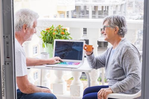 Fotografie, Obraz  couple of seniors on the terrace having fun and enjoying - man with laptop  show