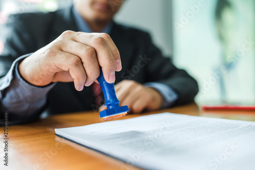 Fotografering Businessman stamping with approved stamp on document at meeting.