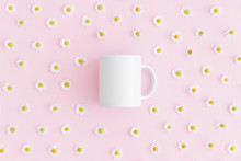 Top View Of A White Mug Mockup With Daisy Decoration On A Pink Background.