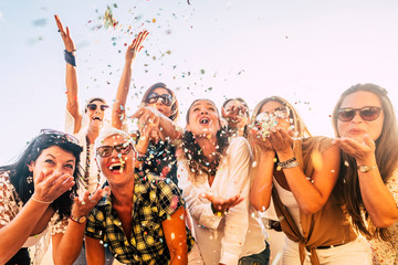 People having fun in party celebration friends concept - group of young and adult women all together laughing blowing coloured confetti - friendship and love for lifestyle with mixed active generation