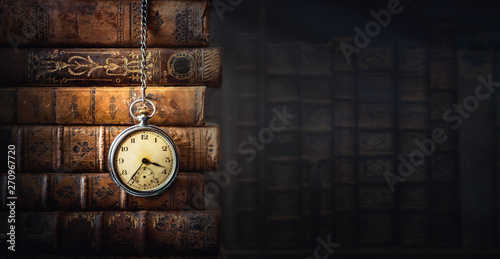 Vintage clock hanging on a chain on the background of old books Wallpaper Mural