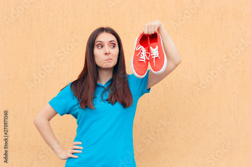 Fotografía  Unhappy Woman Holding a Pair of Red Sport Shoes