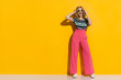 Leinwanddruck Bild - Happy Stylish Woman In Sunglasses, Pink Wide Legs Trousers, Sneakers And Striped Blouse Is Shouting