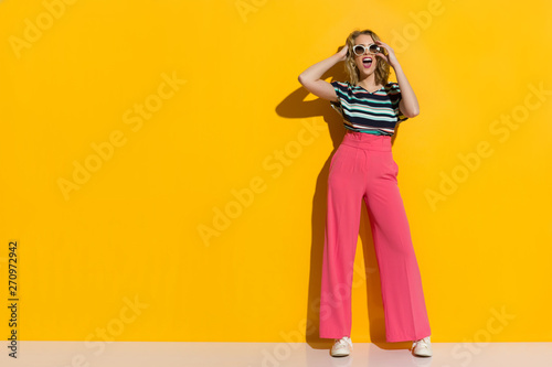 Happy Stylish Woman In Sunglasses, Pink Wide Legs Trousers, Sneakers And Striped Wallpaper Mural