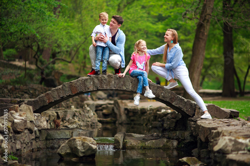 Foto auf AluDibond Camping Happy young family with children in summer green park on stone bridge over the river in forest