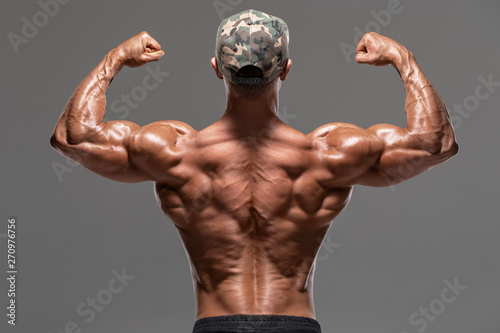 Fotografie, Tablou  Rear view muscular man showing back muscles and biceps, isolated on the gray background