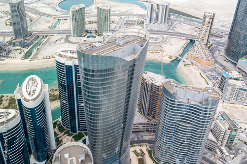 Fotografie, Tablou  Aerial drone shot of skyscrapers and towers in the city - Abu Dhabi Al Reem isla
