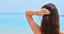 Brunette Girl Sunbathes On The Background Of The Sea. Copy Space. She Holds Her Hair With Her Hand So It Is Not So Hot.