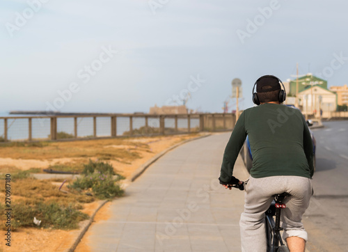 Fotobehang Antarctica rear view of a man with headphones riding the bicycle by the sea