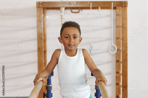Fotografia, Obraz  Positive smiling black dark skinned boy in white tank top exercising on two wooden parallel bars at gym, performing routine, doing support position