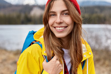 Cropped Image Of Lovely Cheerful European Woman Has Broad Tender Smile, Long Straight Hair, Wears Red Hat, Yellow Anorak, Has Rucksack On Back, Poses Over Blurred Nature Background In Open Air