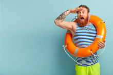 Surprised Young Holiday Maker With Red Hair And Beard, Comes On Beach With Safety Equipment As Cannot Swim, Keeps Hand On Forehead, Focused Into Distance, Shocked To See Drowning Man In Sea.