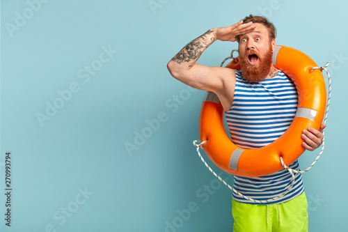 Foto Surprised young holiday maker with red hair and beard, comes on beach with safety equipment as cannot swim, keeps hand on forehead, focused into distance, shocked to see drowning man in sea