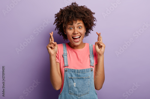 Carta da parati  Glad smiling woman wishes luck, feels thrilled emotions, keeps fingers crossed, dreams about getting promotion, hopes for something desirable, isolated over purple background