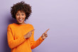 Photo of delighted African American woman points away with both index fingers, promots awesome place for your advertising content, isolated over purple background, gives advice, shows copy space