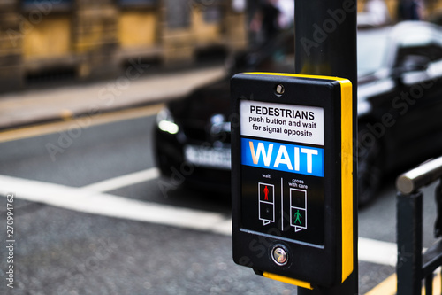 Fotografiet Pedestrian Crossing button in Leeds City Centre that says WAIT for people to cro