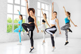 A group of people jumping to dance in a dance class. The concept of sports, a healthy lifestyle, fitness, stretching and dancing