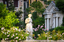 Scenic View Of A Street In Venice, Italy. Old Houses With Beautiful Garden On Grand Canal In The Venice Center. Classic Marble Statue In Flower Garden In Summer. Nature And Architecture Of Venice.