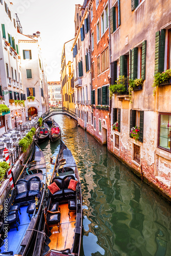 Photo Stands United States Street with moored gondolas and cafe, Venice, Italy. Scenic view of the Venice canal in summer. Colorful vintage houses of Venice with flowers. Romantic tourist water trip in the old Venice city.