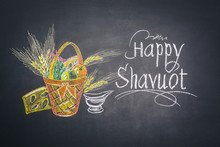 Happy Shavuot (Feast Of Weeks) Greeting Design With Milk And Fruits Basket On Chalkboard.