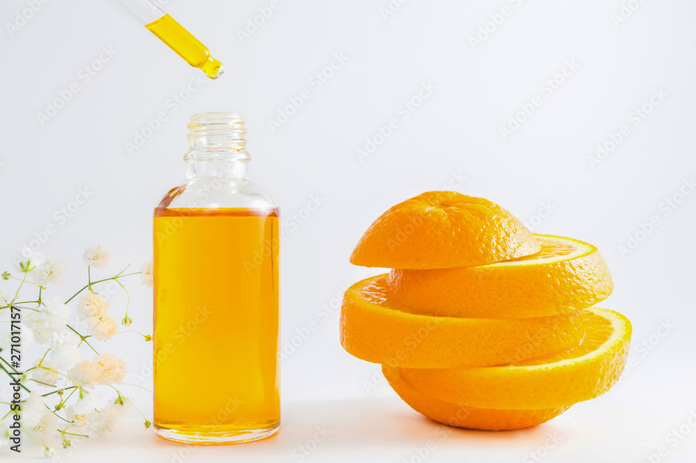 Fototapeta Vitamin C serum in cosmetic bottle with dropper, sliced orange and flowers on white background. Organic SPA cosmetics with herbal ingredients.