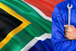 canvas print picture - Mechanic in blue uniform is holding wrench against waving South Africa flag background. Crossed arms technician.