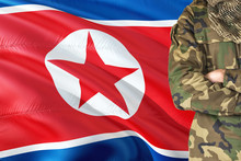 Crossed Arms North Korean Soldier With National Waving Flag On Background - North Korea Military Theme.