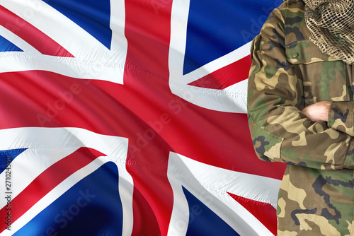 Tela Crossed arms British soldier with national waving flag on background - United Kingdom Military theme