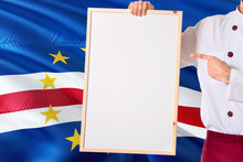 Chef Holding Blank Whiteboard Menu On Cape Verde Flag Background. Cook Wearing Uniform Pointing Space For Text.