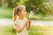 Girl blowing at dandelions