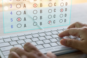 Dry hand of adult student using white keyboard on table to do test examination with multiple choice questions on virtual screen at home. Education futuristic technology and Lifelong learning concept.