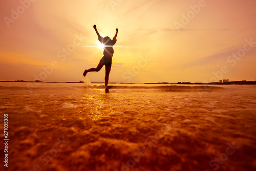 Foto  freedom asian beautiful woman  happiness jump and dance with sunset beach backgr