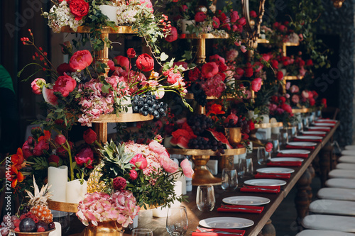 Wedding table flowers with fruits and berries decor in red white pink green colors.