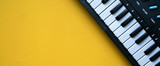 close up top view electric keyboard music instrument on yellow background concept