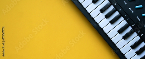 close up top view electric keyboard music instrument on yellow background concept - 271047976