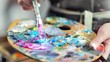 Close-up professional painter hands mixing color paint on palette creating amazing picture